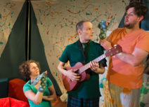 Production image from '5 More Minutes'. On the left, a lady in a green tshirt is kneeling on the floor with a green, spotty snake hand-puppet on her hand, next to her is a man in a green polo shirt holding a guitar, he is looking at a man next to him who also has a green, spotty snake hand-puppet and is wearing an orange t-shirt