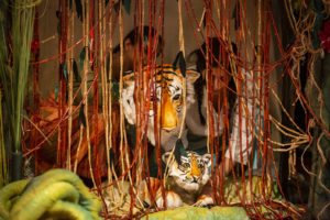 Two tiger puppet faces behind jungle vines