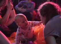 A baby wearing a long-sleeved animal print t-shirt is crawling through some orange mesh and pointing towards an adult wearing a grey tshirt
