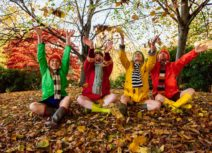 Production image for '4 Go Wild in Wellies'. Four adults are sitting cross-legged in a wooded area on a bed of Autumn leaves, they are all throwing leaves up into the air and are wearing scarves, wellies and colourful raincoats