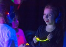 Three children wearing headphones and holding glowsticks. Their clothes are glowing as they are standing under UV light. You can see one child's face clearly, she is blonde and has a happy and surprised expression on her face.