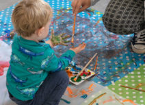 A toddler wearing a green, dinosaur-print tshirt is crouched on plastic table cloths which are covered in paint. An adult is crouching in front of him painting more paint onto his hands with a paintbrush.