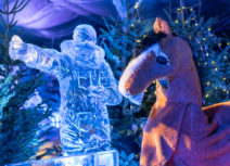 Picture of pantomime horse who is brown with a white nose and white lower legs, the horse is standing in front of a sculpture made of ice and a Christmas tree