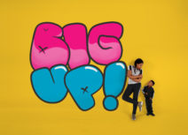 Production image for 'Big Up!'. The word 'Big' is written in large pink cartoon bubble writing and the word 'up!' is written below it in the same font but in blue. A teenage girl is leaning against the exclamation mark at the end of the word 'up' looking down at a younger, shorter boy.