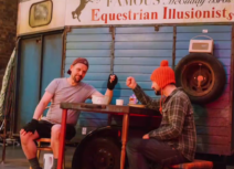 Production image from 'Black Beauty', they are both sitting down in front of a blue horse box and are bumping fists. One man is wearing a red bobble hat and a checked shirt, one is wearing a black baseball cap worn backwards and a grey tshirt