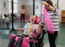 Image of woman who is a wheelchair user laughing with a woman standing next to her with a piece of fabric