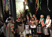 Photo taken at Family Jam in Z-arts cafe of a group of men and women wearing colourful clothes playing on individual drums