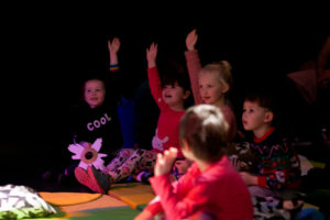 Photo from a previous Drag Queen Story Time show. Photoof five young children sitting on the floor with their hands raised in the air