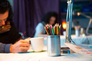 Photo of woman sitting at a table drawing with coloured pencils
