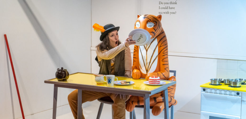 A woman wearing a hat with an orange feather in it is sitting down at a yellow dinner table, she is sitting next to a statue of The Tiger from The Tiger Who Came to Tea and she is holding a plate up to the tiger'sface.