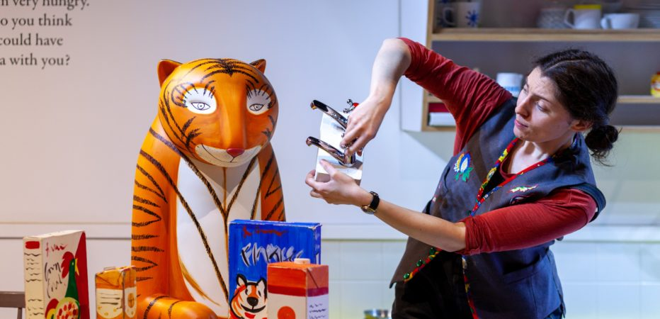 Photo of a woman with brown hair wearing a blue waistcoat and red long-sleeved t-shirt. She is in the middle of telling a story. She is stood next to a statue of The Tiger from Z-arts interactive exhibition. The Tiger is sat at a table, on the table is a box of Frosties and a carton of orange juice.