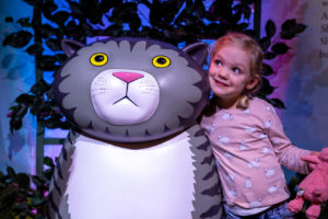 Promo image for Meet Mog Live event. Photo of a young girl with blonde hair wearing a pink long-sleeved tshirt and denim shorts. She is standing next to a stature of Mog the Forgetful Cat which features in Z-arts interactive exhibition