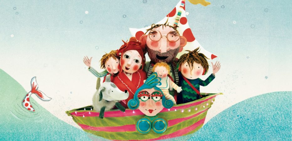 Arthur's dream boat promo image. Cartoon image of a green and red boat with a red and white spotty sail floating on the sea. There are six people crowded on to the boat and they are waving, they look happy.