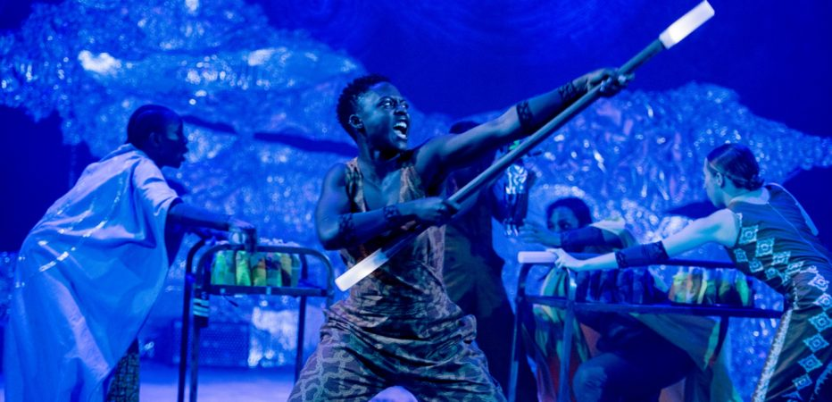 Production photo, the stage is lit in blue - in the foreground a women in a printed jumpsuit is brandishing a large stick with illuminated ends. Her facial expression looks as though she is shouting.