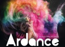 Photo of a young woman pictures in profile flipping her hair back, there is a multicoloured cloud of powder paint billowing out around her