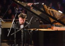 Photo of a man sat playing a grand piano. He has short brown hair and is wearing a tuxedo.