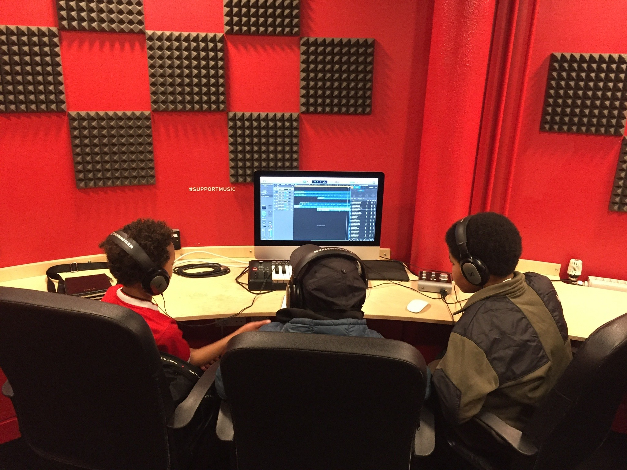 Photo of three boys sat in front of a mac desktop computer. There is a red and black check patterned wall in the background