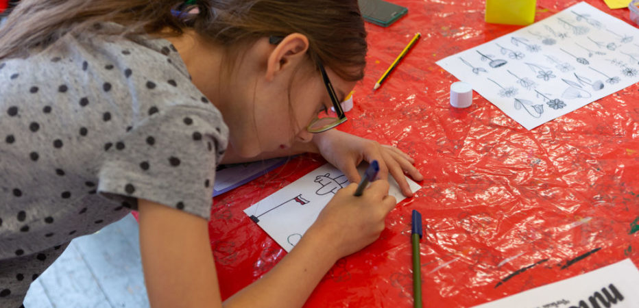 Girl with long brown hair and a grey spotty tshirt leaning over a table drawing on a piece of paper
