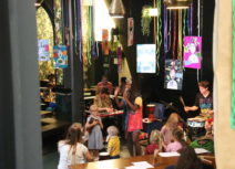One Manchester Family Jam promo image. A woman is standing singing in front of an audience of young families. She is wearing a colourful dress and there are multicoloured streamers floating down from the ceiling above her head.