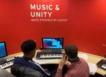 "Lead image for songwriting competition. Two young people are sitting in front of a music keyboard and a computer screen, behind the screen is a red wall that says ""music and unity"" on it."