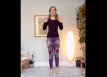 Lead image for Let's Yoga. Photo of a woman standing up wearing purple patterned leggings and a dark long-sleeved top waving at the camera.