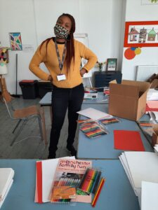 Yemi standing, surrounded by Art Packs